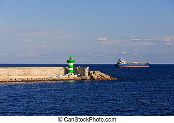 Tanker Passing Barcelona Seawall - A green and white...