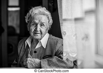 An elderly woman, black and white portrait of sitting at the table.