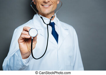 Close up of male doctor holding diaphragm of stethoscope -...