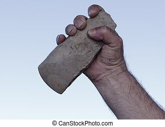 filthy hand holding handaxe - filthy hand of caveman holding...