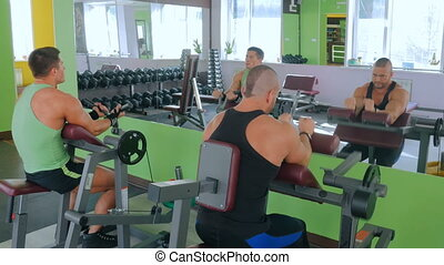 Two athletic young men working out on fitness exercise equipment at gym
