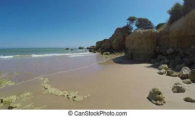 Walk along the summer Portuguese beach Olhos de Agua,...