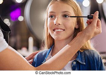 Close up of makeup artists hands applying mascara