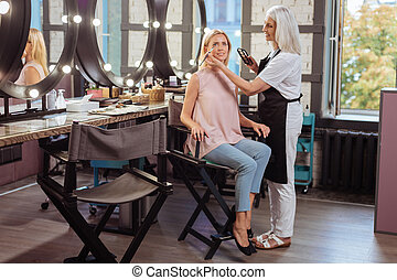 Smiling woman having eye shadows applied by makeup artist -...
