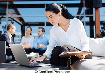 Serious pleasant woman looking at the laptop screen -...