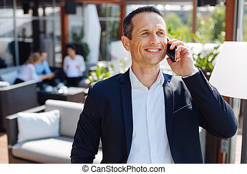 Delighted positive man having a pleasant phone conversation