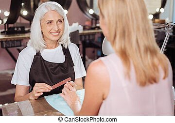 Charming manicurist smiling at her client while filing nails...