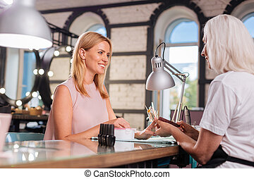 Senior manicurist chatting with her client while doing her...