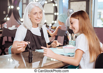 Manicurist and teenage client agreeing on nail polish -...