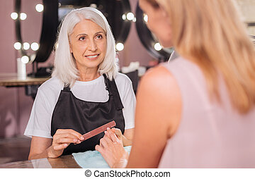 Senior manicurist looking at her client while filing nails -...