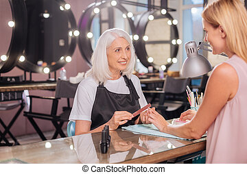 Senior manicurist and her client exchanging smiles -...