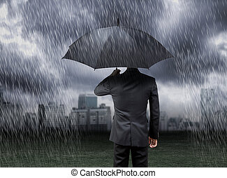 businessman hold umbrella under rain storm with city...