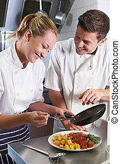 Chef Instructing Trainee In Restaurant Kitchen