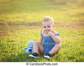 cute little girl is sitting on the grass in a park with a...