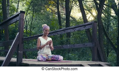 Woman sitting on the old bridge with singing bowl -...