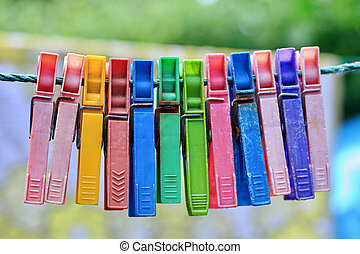 Colorful group of very old and used clothespins on a rope