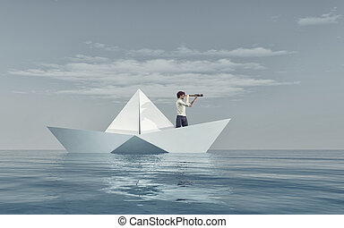 Man watching through a spyglass in a paper boat afloat the...
