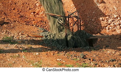 Cinemagraph of Concrete poured into a pit in the ground from...