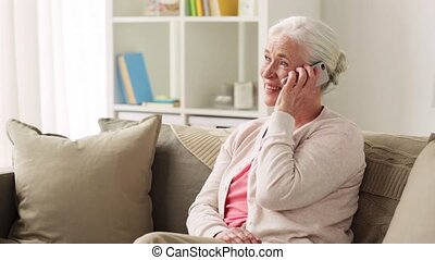 senior woman with smartphone calling at home - technology,...