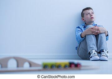 Boy starring at wall - Boy in blue shirt sitting on floor...