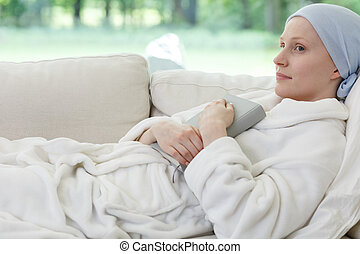 Woman with ovarian cancer lying on sofa holding book in...