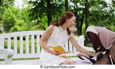 mother with baby in stroller reading book at park - family,...