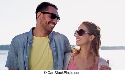 happy couple in sunglasses hugging over sea - love,...
