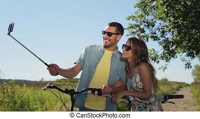couple with bicycle and smartphone selfie stick - people,...