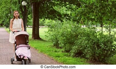 mother with baby in stroller at summer park - family,...