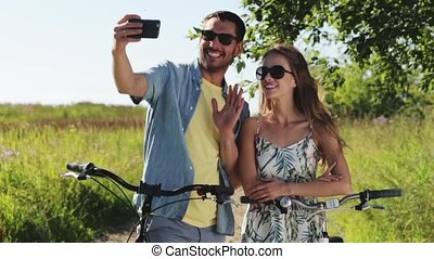 couple with bicycle taking selfie by smartphone - people,...