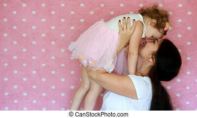Mom and daughter. Motherhood. Mother and child play, hug and kiss,motherly love