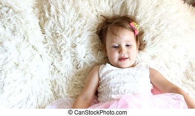 Funny little girl lying in bed smiling and laughing, looking...