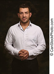 Portrait of handsome man looking at camera. Black background