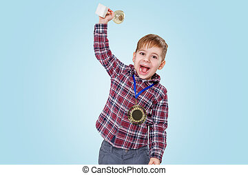 Cheerful little boy showing trophy cup and wearing golden...