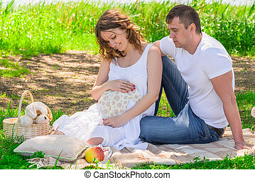 Family in anticipation of a child, rest near a lake in a park on a picnic