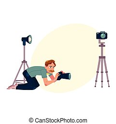 Photographer, camera man taking pictures, shooting from low angle, kneeling