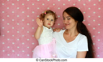 Mom holds her daughter in her arms. Mother and child Wave hands goodbye