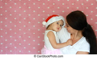 The mother is holding a daughter in the cap of Santa Claus. Christmas. New Year