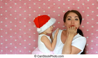 Mom and baby in the cap of Santa Claus sending an air kiss. Christmas