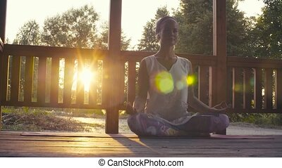 Attractive woman doing yoga asanas on sunset - Gold time...