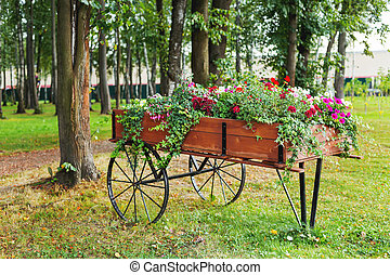 Flowerbed shaped as a wooden cart. Garden decoration with...