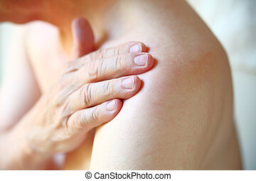 Man indicates area of pain on shoulder - Senior man with...