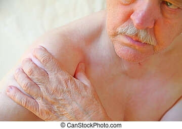 Senior man grips his sore shoulder - An older man with a...