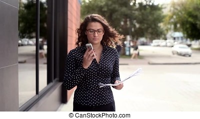 Business woman walking next to the office talking on the phone celebrating her success and throwing documents in the air
