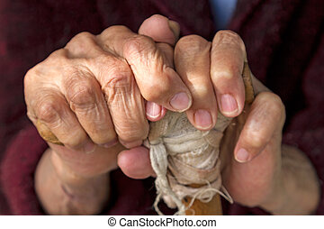 Hands of an old woman on a wooden crutch closeup