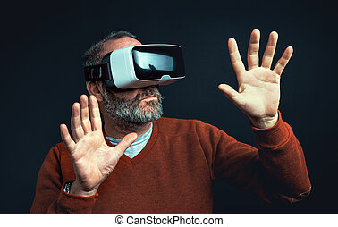 Mature business man wearing virtual reality googles / VR...