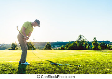 Experienced male golfer hitting the golf ball towards the...