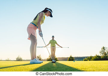 Fit woman exercising hitting technique during golf class...