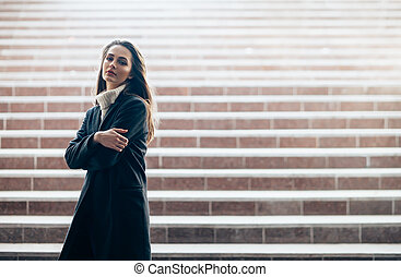Sensual beautiful woman standing alone on underground stairs...