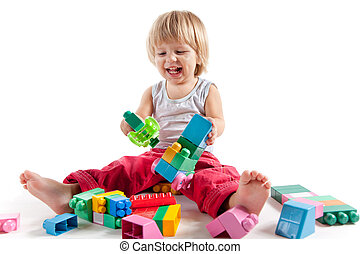 Laughing little boy playing with colorful blocks - Laughing...